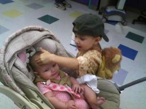 Jayden, backpack on, patting baby sister